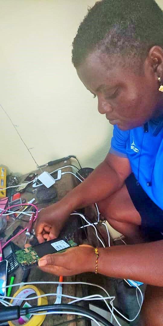 Viviane Tiega en train de reparer un téléphone portable