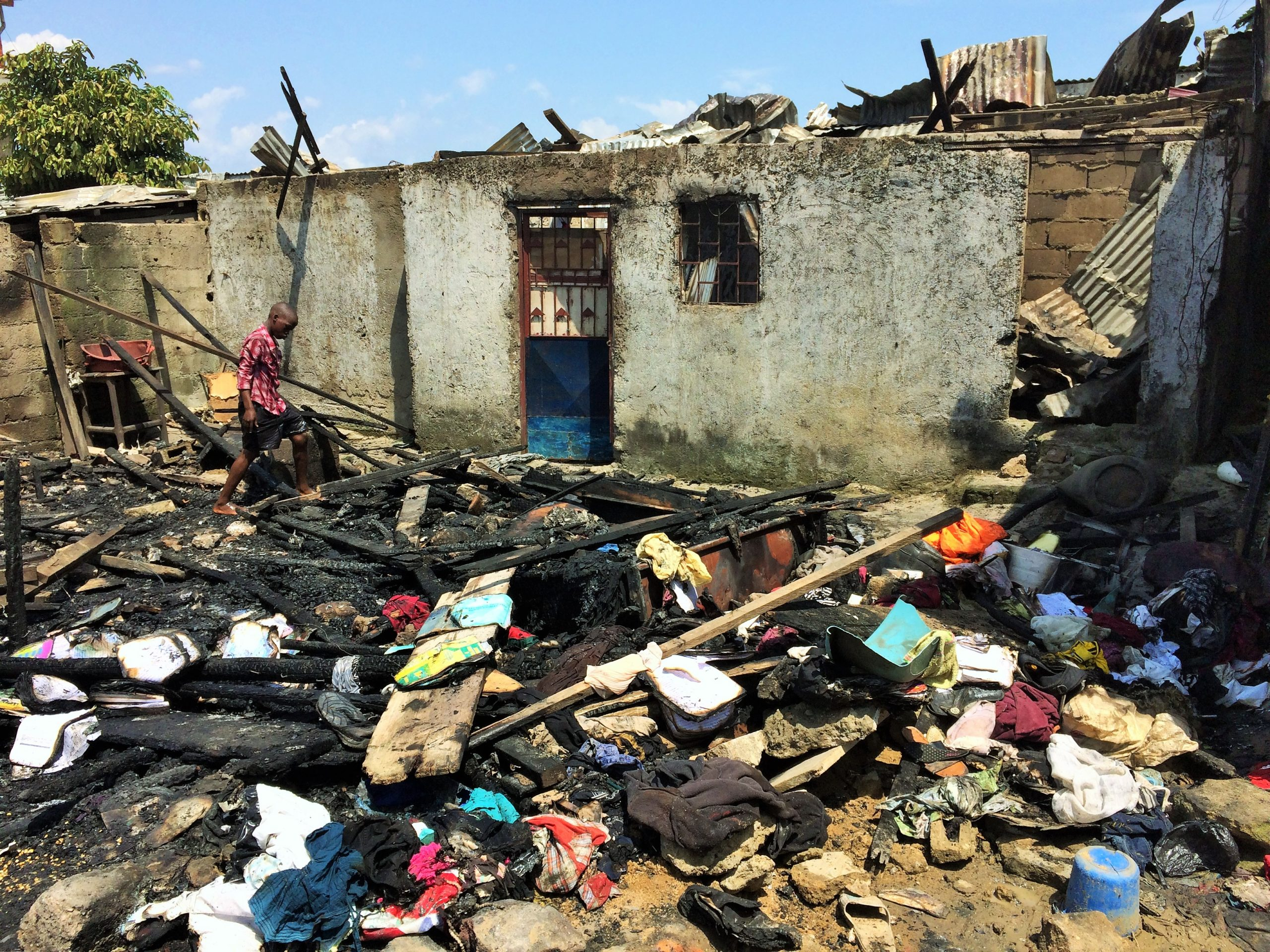 Douala, samedi 10 avril 2021. Un enfanf fouille dans les décombres sur le lieu de l'incendie au quartier Bépanda Omnisports. Crédit Photo: Moustapha Oumarou