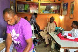 Abdoulaye-Mohamadou-tee-shirt-violetdans-son-atelier-de-couture-en-train-de-repasser-le-boubou-dun-client-a-quelques-jours-du-Ramadan-2021